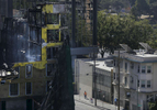 A person in safety gear walks past an evacuated apartment building across the street from the smoldering remains of a seven-story building July 8, 2017 which had been under construction that was completely destroyed in a massive fire in downtown Oakland, Calif.