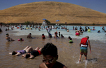 People lounge and play in Contra Loma Swim Lagoon to escape the 100 degree heat June 21, 2017 in Antioch, Calif.