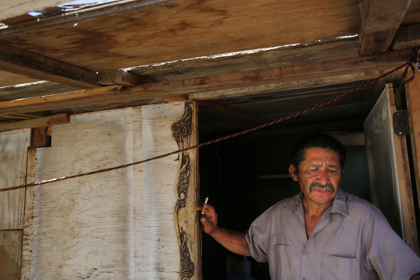 While trying to shelter from triple digit heat, Martín Hernandez Mena, 50, smokes a cigarette as he stands in the doorway of the home he built in the shantytown. Mena has lived for a year and a half in the canal bed. He moved after he could no longer afford rent in town because work was becoming more and more scarce.