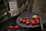 A collection of donated tomatoes lay strewn about a cooking area next to a folded sign from the landowners warning people to stay off the land outside of Mario Rodriguez's home in the shantytown. More than 40 percent of about 11,500 people in Mendota live below the poverty line.