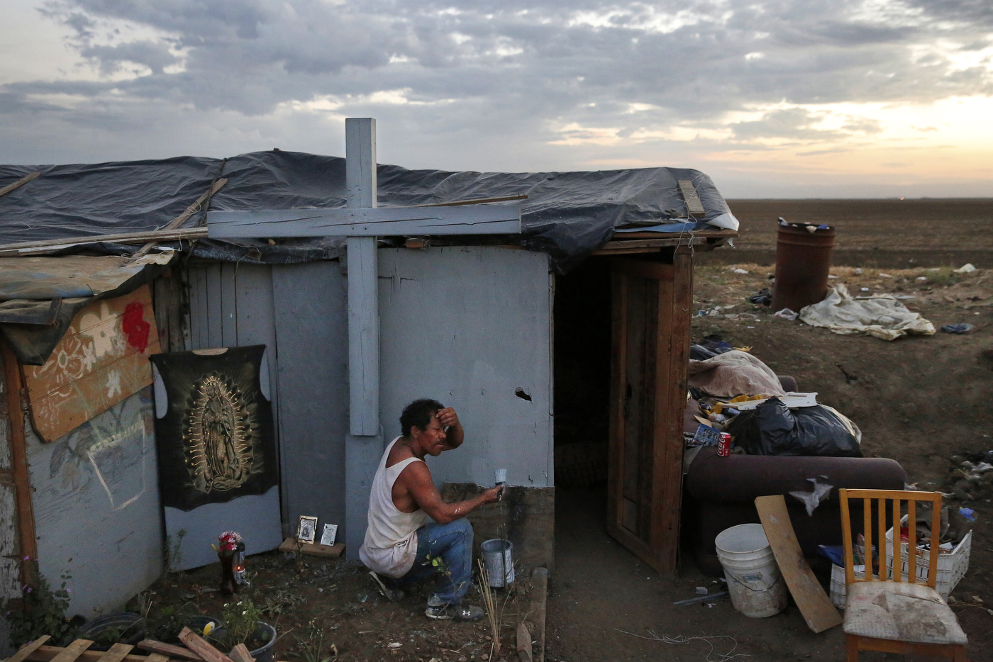 As evening falls in the shantytown, Edgar Torres Castro, 40, paints the outside of his home. Castro likes to save books from the trash and also plants various fruit trees around the encampment. He says that God told him to live out in the shantytown.