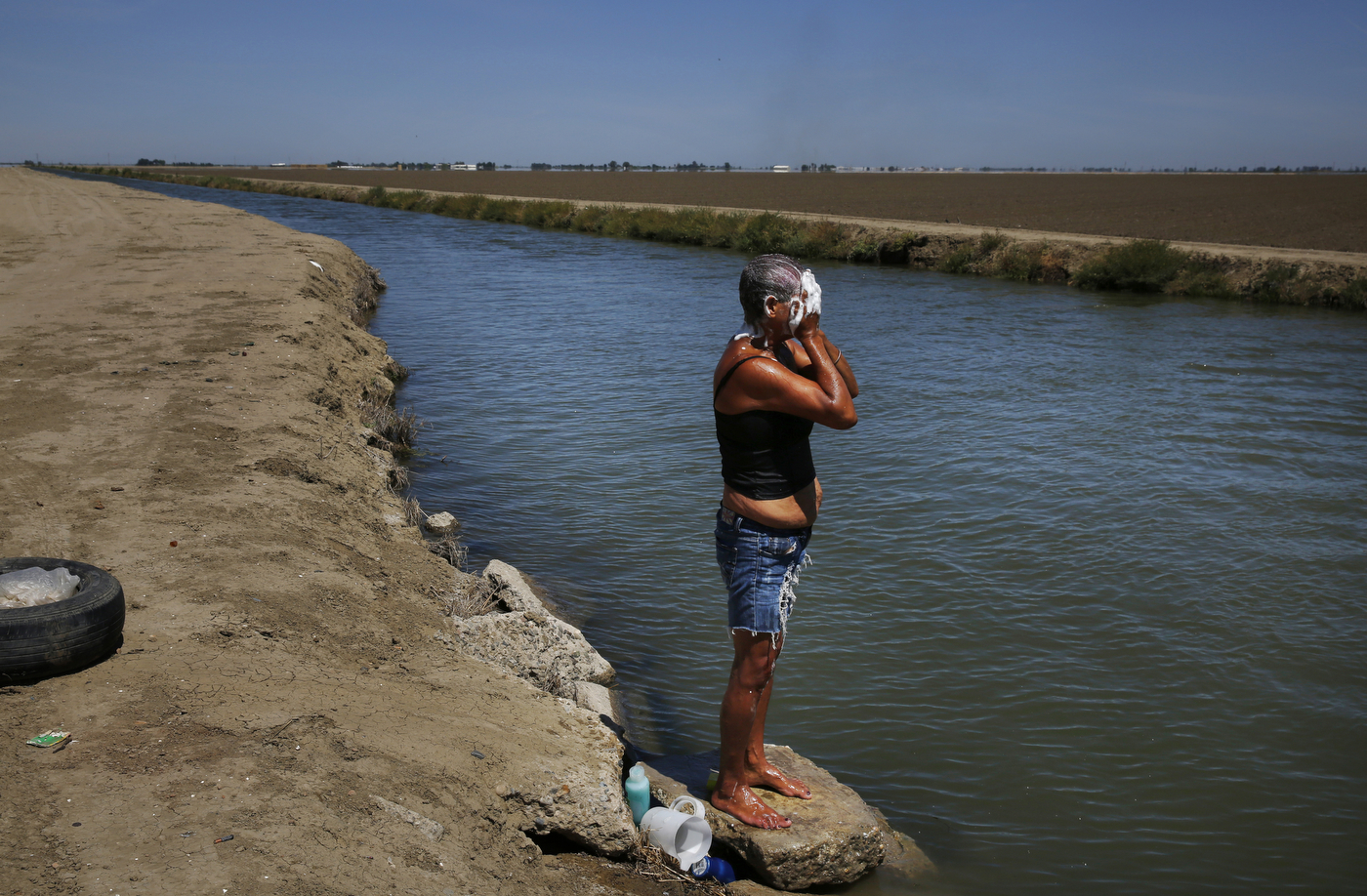Sandoval washes her face and hair in the nearby irrigation canal. The canal is the only source of water for the shantytown residents if they want to bathe, cool down, or wash their clothing. They have to buy water from a nearby store in town for drinking and cooking.