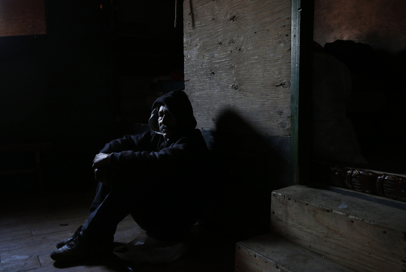 "Mena sits in the chilly air inside of his home as he waits for the police to show up to evict him and the other residents from the shantytown. {quote}I keep thinking and hoping of finding ways to get out of this canal. Once I'm free from that, I can focus on other things."" Mena said in Spanish. ""All your energy goes to just getting by here.{quote}"