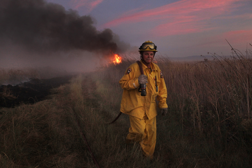 A firefighter works to put out a large brush fire July 24, 2014 that sprang up outside of Merced, Calif.