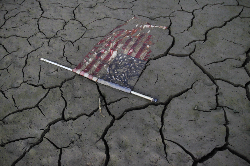 An American flag lays perfectly flat on the freshly exposed bottom of Lake McClure as it sits at about 8 percent capacity Sept 28, 2014 in Snelling, Calif.