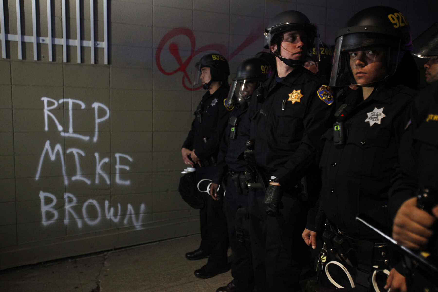 Police officers push people back from the 580 westbound ramp during a protest against the grand jury's decision not to indict the white police officer who fatally shot an unarmed black teenager months ago in Ferguson Nov. 24, 2014 in Oakland, Calif.
