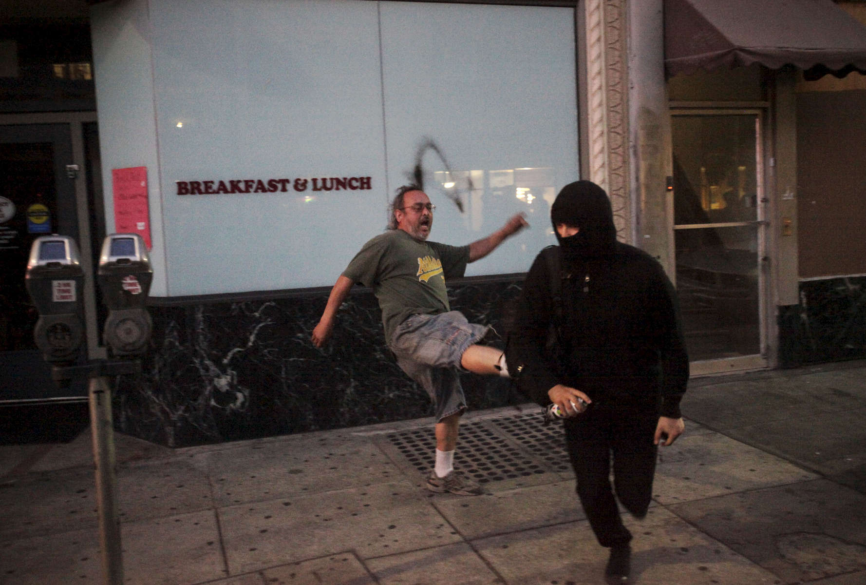 Ralph Guerra, 53, runs off a protester after the person tried to spray paint on a window during an {quote}F the Police{quote} march held in solidarity with Ferguson, Mo., where there was a fatal shooting of an unarmed 18-year-old black man earlier in the week August 15, 2014 in Oakland, Calif.