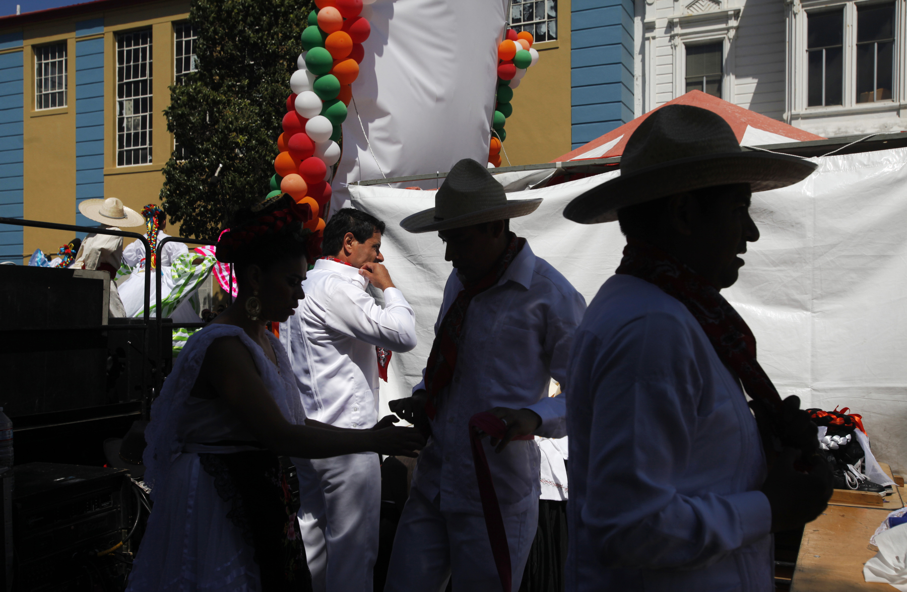 From left, members of Ensambles Ballet Folklorico de San Francisco, Maricela Benavides, Marco Castellanos, Mario Sosa and Arturo Flores change costumes as other dancers perform on stage during the annual Cinco de Mayo celebration May 3, 2014 along Valencia street in San Francisco, Calif.