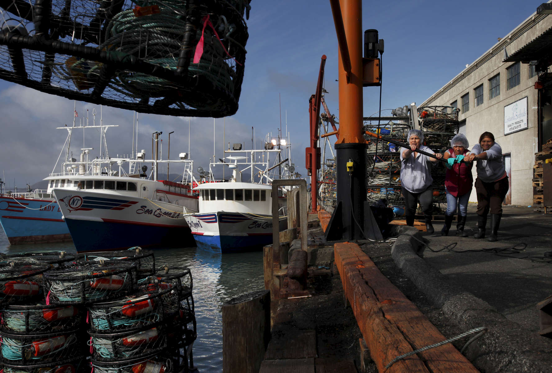 Dock workers, from left, Virginia Flores, Martha Bustamante and Ingrid Orecaba operate a hoist to help the Ingot load up crab traps or {quote}pots{quote} on Pier 45 Nov. 14, 2014 as the crab season starts in San Francisco, Calif.
