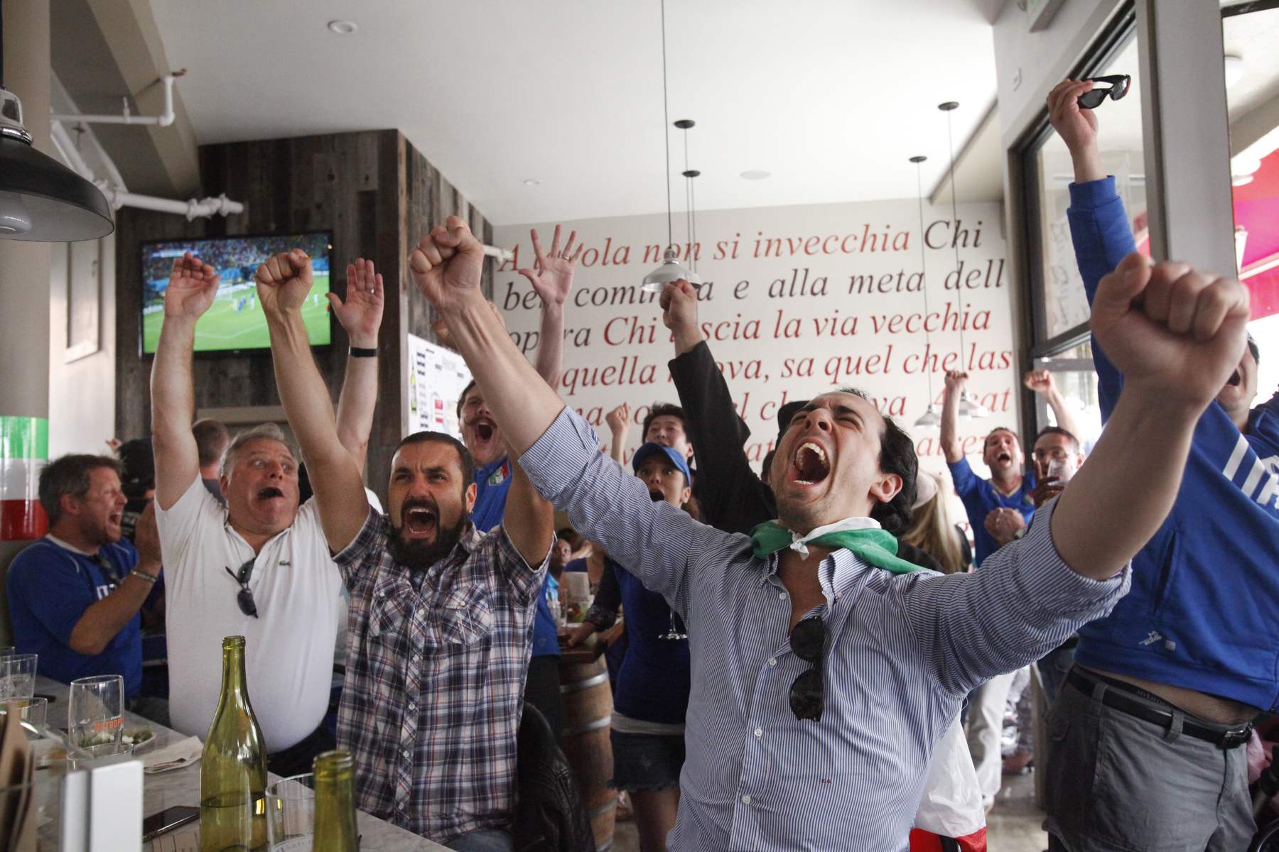Italy fans Emanuele Gastel, 25, right, cheers with Savino Cancellara, 30, center, and Vince Lamanna, far left, after Italy scored the first goal during the England vs. Italy World Cup match June 14, 2014 at Il Casaro in San Francisco, Calif.