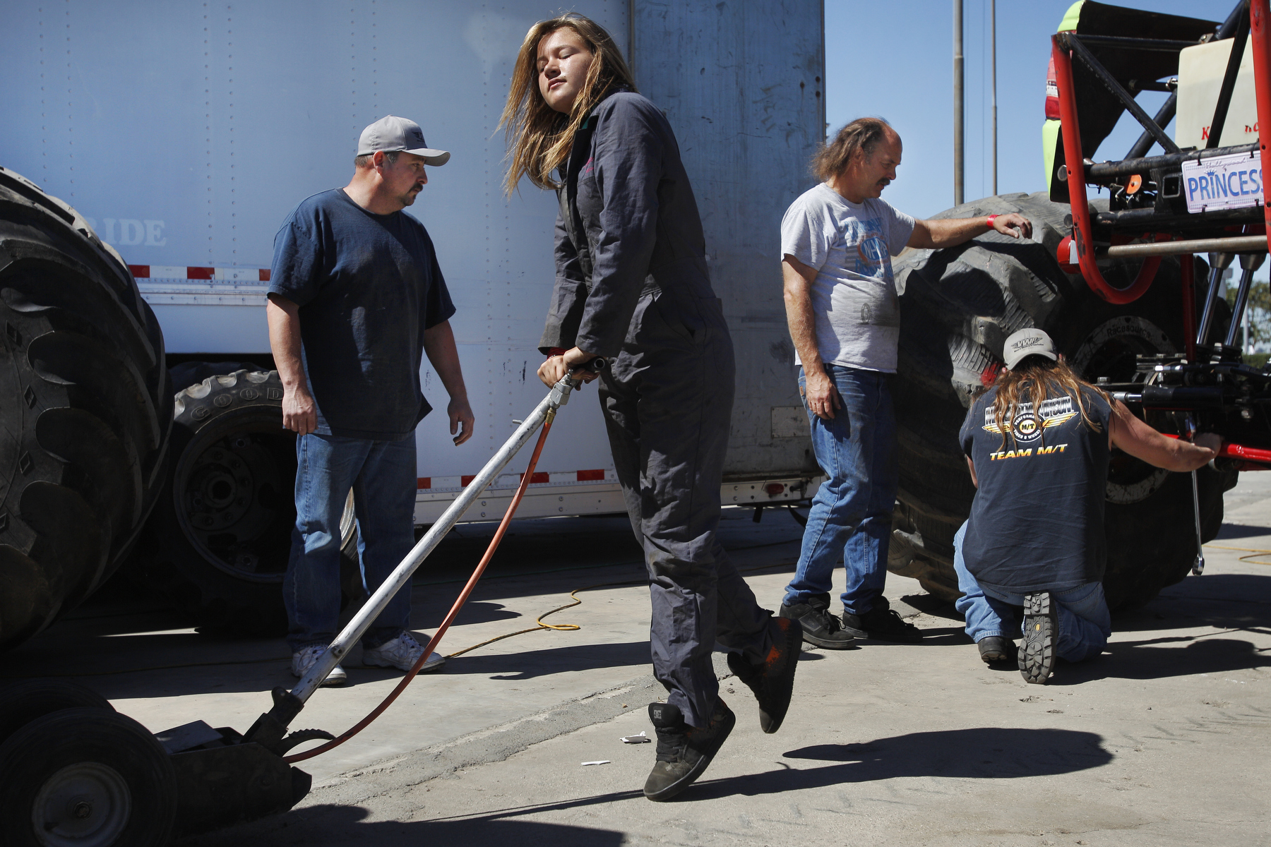 Rosalee Ramer, 16, throws all of her weight onto the handle of a floor jack, using it to raise up her father's monster truck so she can put monster wheels on it as Guillermo Serrano, left, Kelvin Ramer (her father), third from left, and Dave Wever work on her truck in preparation for their evening performance.