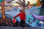 Sekou Carson adjusts the hat on his son Zakai Carson, 4, as they lean up against a community mural titled {quote}How Do You Shine{quote} while the two were out for a walk during Sekou\'s visit to the neighborhood to see his son July 3, 2014 in the Visitacion Valley neighborhood in San Francisco, Calif. {quote}My heart goes out to him and his family,{quote} Sekou said of the shooting, adding that he didn't feel the neighborhood was more unsafe now. {quote}I think it was an isolated incident,{quote} he said. Last Friday, June 27, outreach counselor Allen Calloway was shot and killed while playing dodgeball with children at a basketball court near Herz playground in Visitacion Valley. Since then, the summer program held at the playground has been closed temporarily and the area has had much fewer children and residents using it.