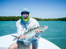 Fisherman holds a bonefish he caught while smoking cigar.