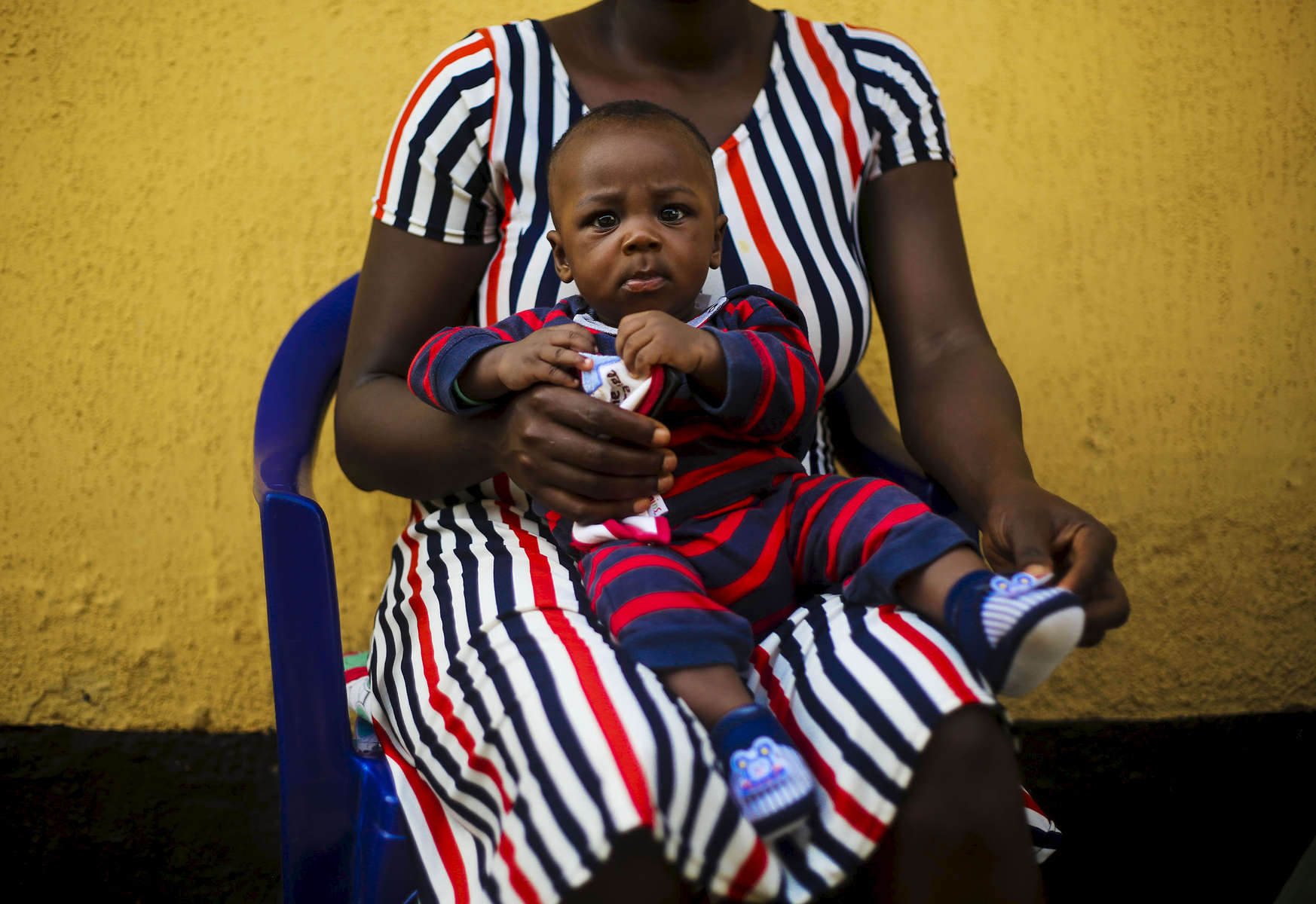 Sitting on his mother's legs, Andrew, 9 months, waits for his vaccination at the medical facility  of Kuchigoro  in Abuja, Nigeria.
