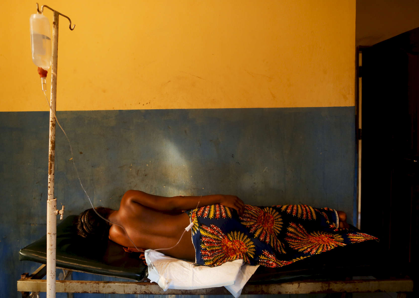 A woman in labor rest on a bed at the medical facility of Kuchigoro in Abuja, Nigeria.