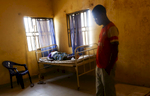 A pregnant woman rest on a bed as she is having bleeding while her husband reflects at the medical facility of Kuchigoro in Abuja, Nigeria.