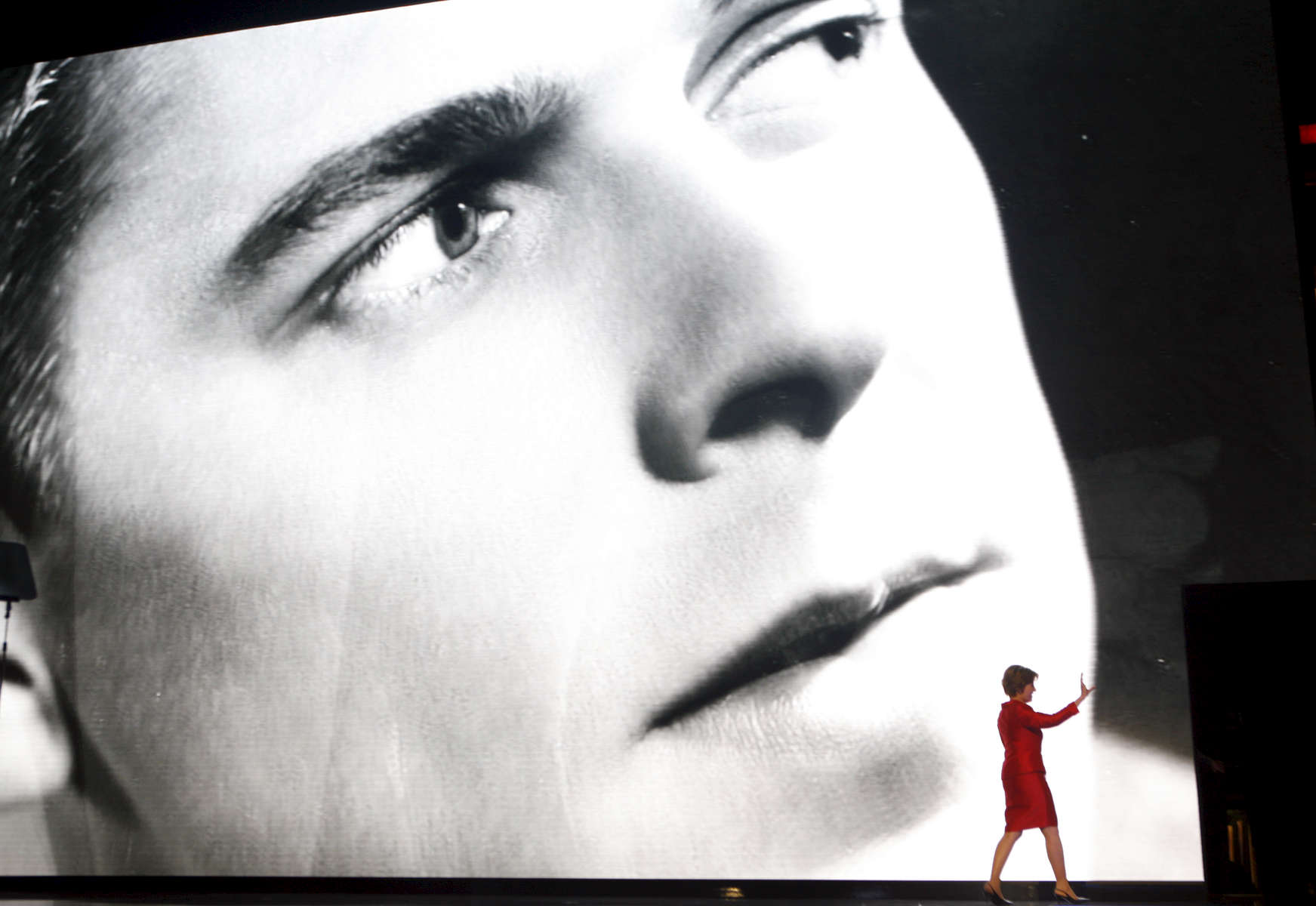 First Lady Laura Bush waves after her speech as a photo of a young Ronald Reagan is screened behind her, during the Republican National Convention at the Xcel Energy Center