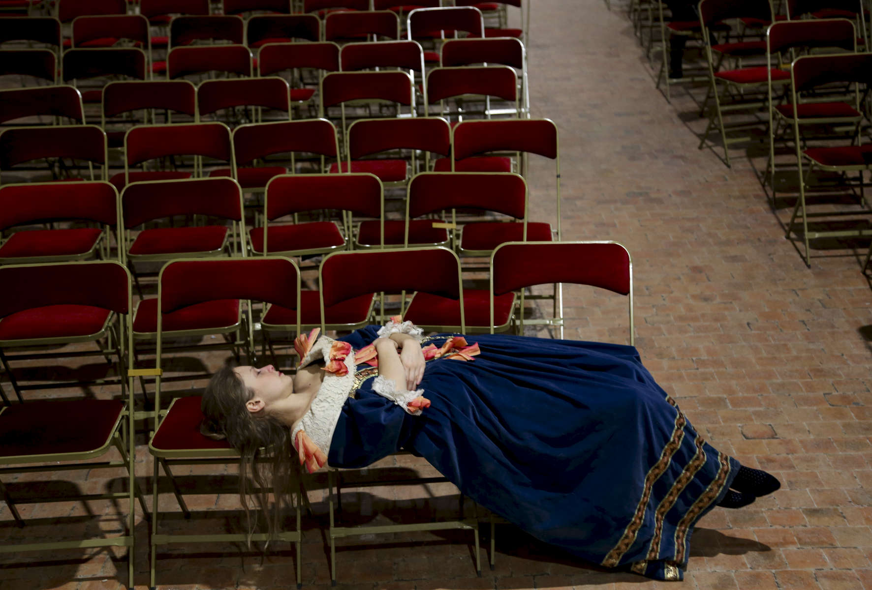 Musician Clémentine Albessard sleeps on chairs between two performances.