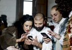 Melodie Veillard, Florent Robin, Romain Falik and Camille Ranciere check their cellphone as the last performance is being transmitted lived on Facebook.