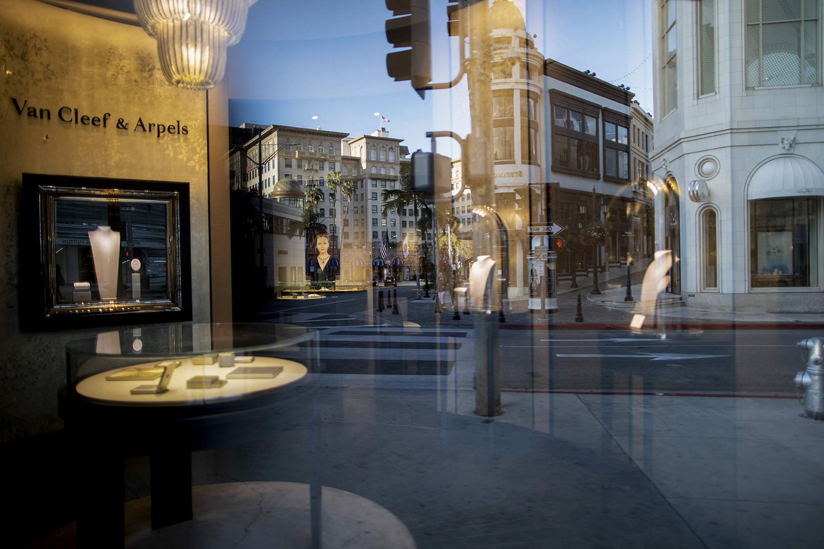 An almost empty Rodeo Drive is reflected on the closed Van Cleef & Arpels window store, in Beverly Hills on March 27, 2020. Governor Gavin Newsom issues a {quote}stay at Home{quote} order on March 19, to slow the spread of Covid-19, closing all the non-essential businesses which include luxury stores.