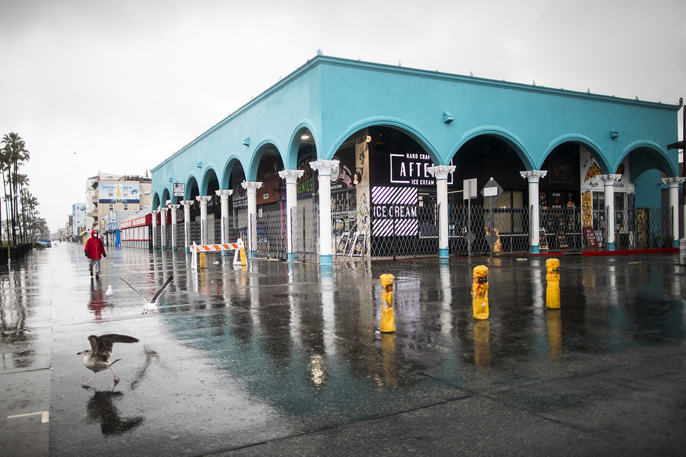 A woman wearing a mask walks in front of closed stores on the Venice Beach Boardwalk on April 9, 2020.  Governor Gavin Newsom issues a {quote}stay at Home{quote} order on March 19, to slow the spread of Covid-19, closing all the non-essential businesses.