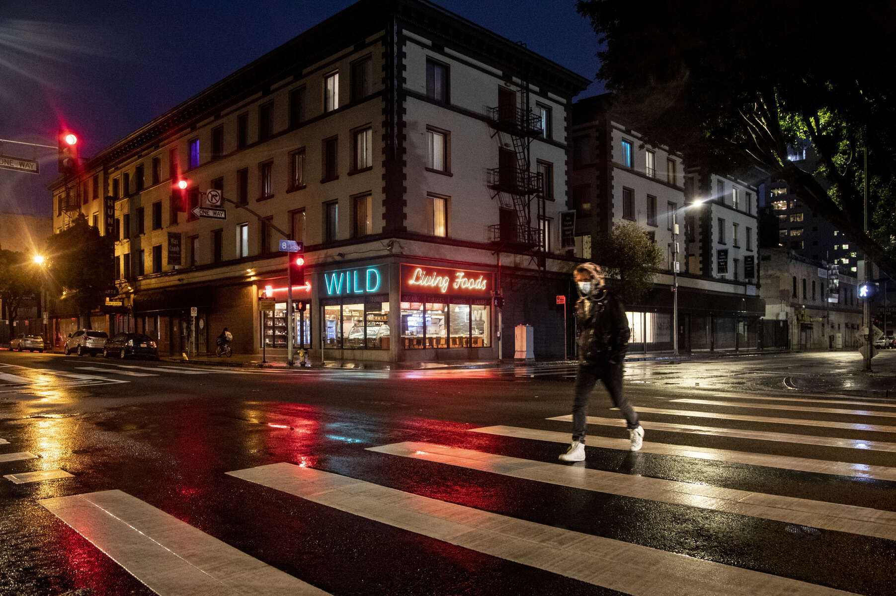 A masked man walks in front of the restaurant Wild Living Foods opened for take out and deliveries in downtown Los Angeles on April 9, 2020.  Governor Gavin Newsom issues a {quote}stay at Home{quote} order on March 19, to slow the spread of Covid-19, closing all the non-essential businesses.
