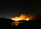 Flames from the Caldor Fire are seen reflected on Caples Lake, near Kirkwood, California, U.S., August 31, 2021.