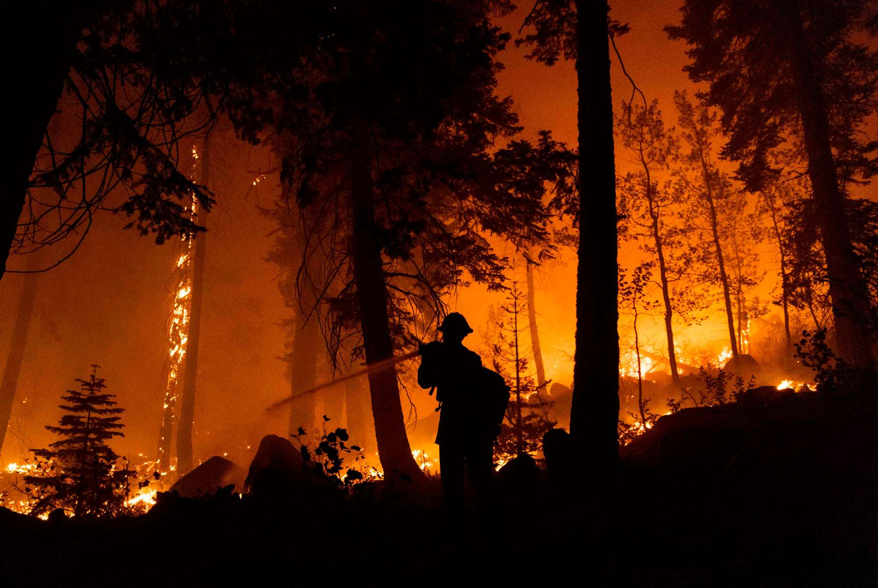Firefighters work to protect houses from the Caldor fire on August 30, 2021, in South Lake Tahoe, California. The Caldor Fire has burned almost 200.000 acres, destroyed over 660 structures and is currently 16 percent contained.