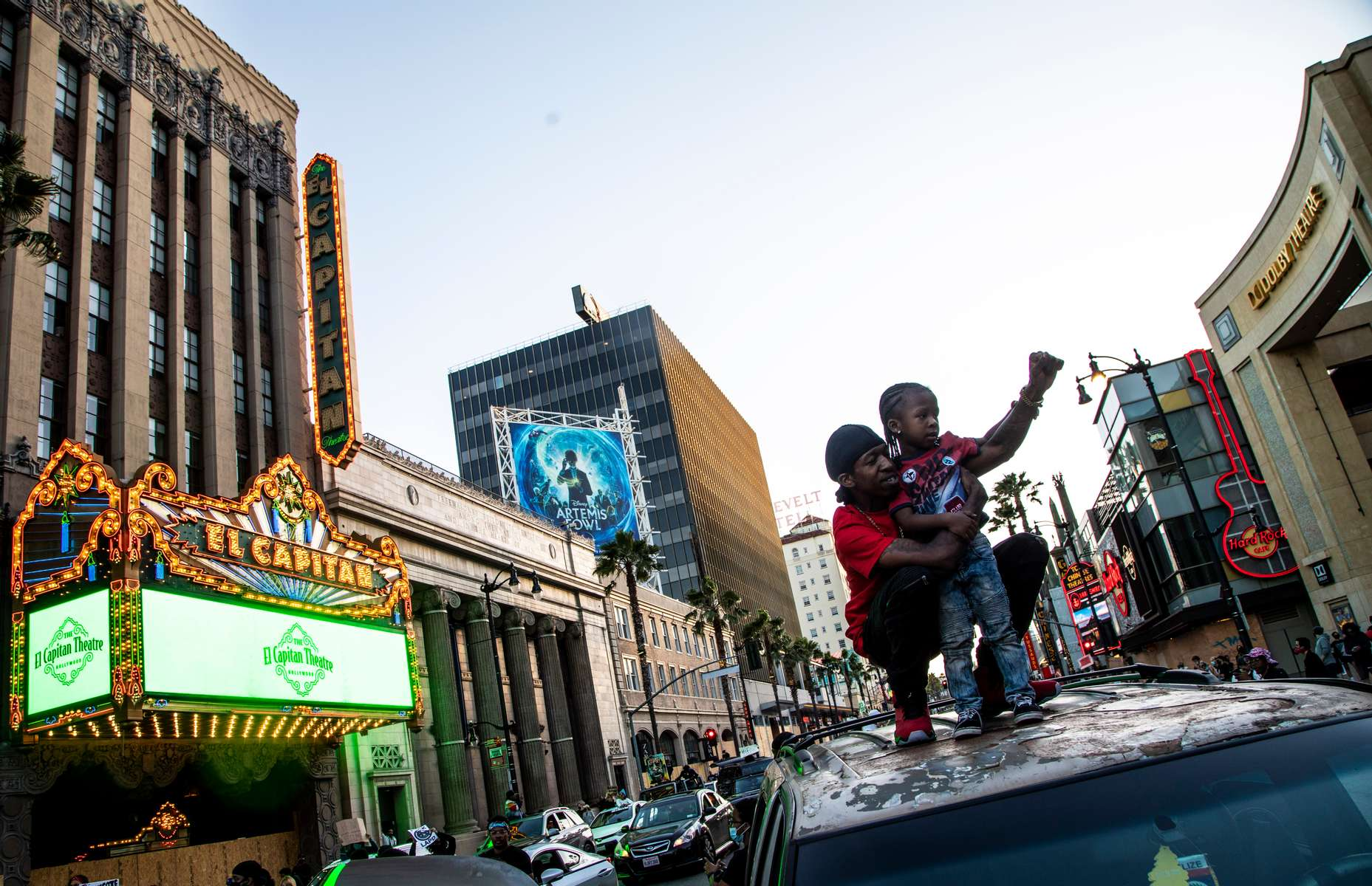 Teady  and his son Zamir stand on top of their car during the march organized by Black Lives Matter on Hollywood Boulevard, on June 7, 2020, in Los Angeles, California. Thousand people attended the thirteen day of protest following the death of George Floyd, an unarmed black man, who died after a police officer kneeled on his neck for several minutes.