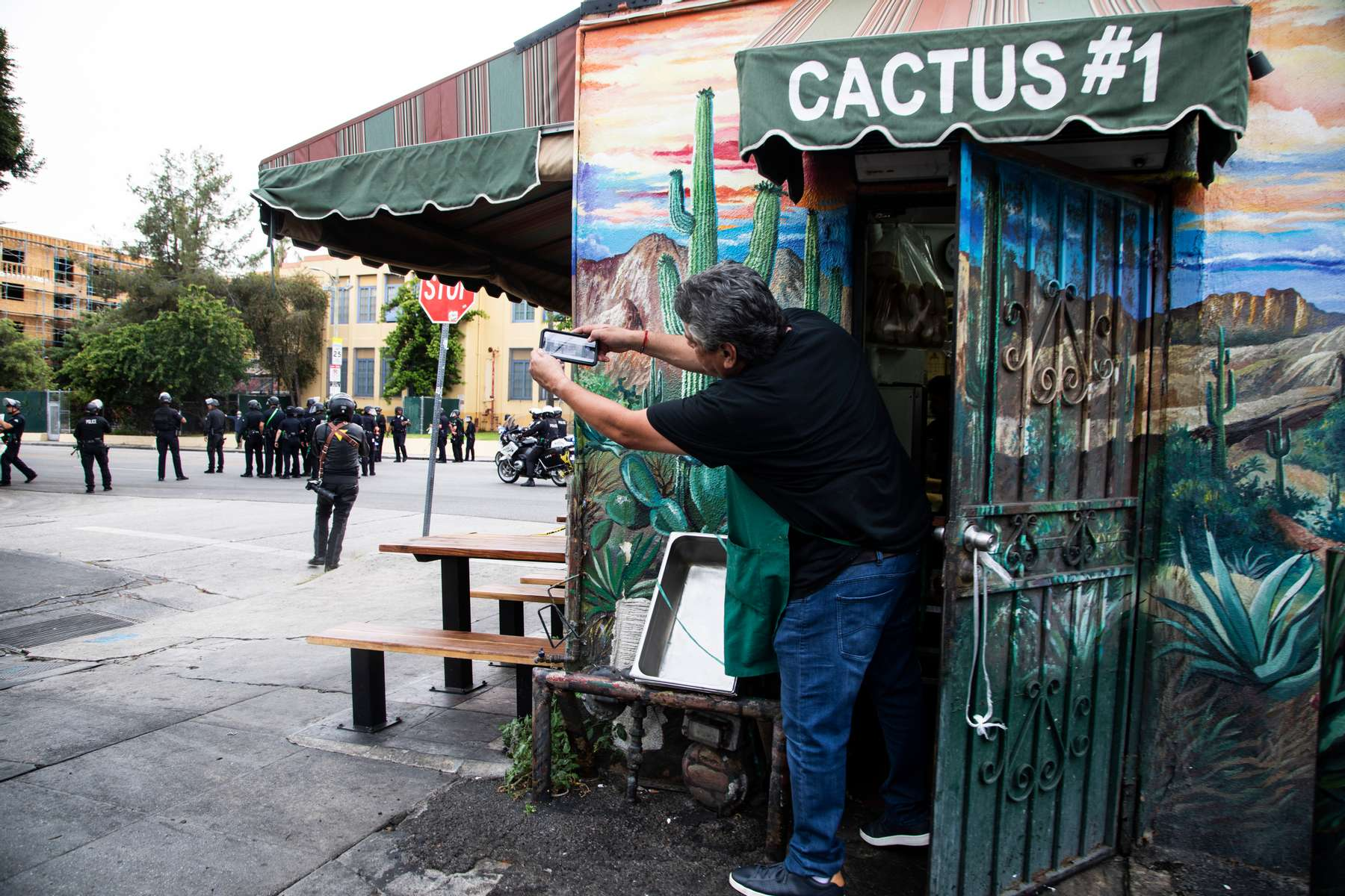 A man get out of his store briefly to take pictures of police arriving to enforce curfew over protesters  during a march over the death of George Floyd, an unarmed black man, who died after a police officer kneeled on his neck for several minutes, in the Hollywood neighborhood on June 1, 2020, in Los Angeles, California.