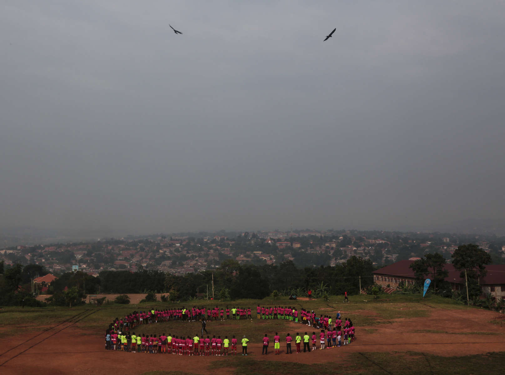 Participants make a big circle at the beginning of {quote}Women take the Lead{quote} festival, a soccer event for Congolese refugee youth in Kampala, Uganda on December 10, 2018.