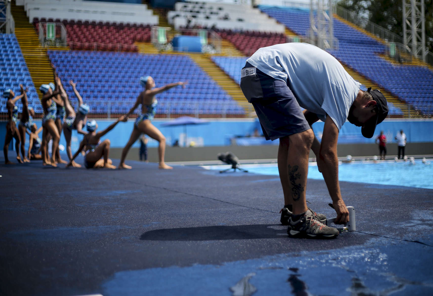 The South African team practices its routine before competing in the Synchronised Swimming Team Free preliminaries while a worker fixes the floor, during the FINA World championships in Budapest, Hungary on July 19, 2017.