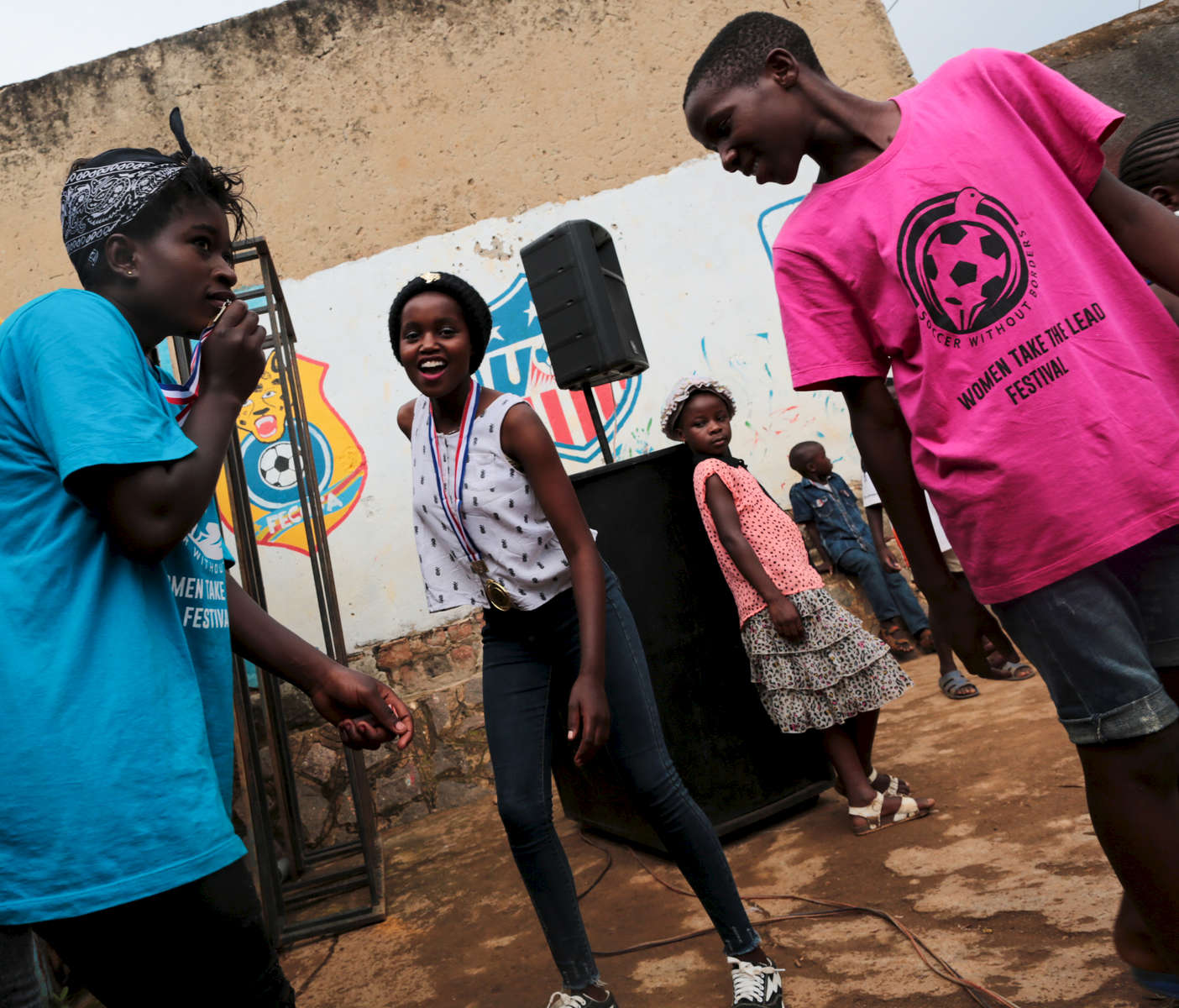 Congolese refugees Ritha (left) and her friend Grace (center) celebrate their medals while their friend Joseph (right) looks up at the end of an award ceremony in Kampala, Uganda on December 18, 2018. Although Uganda is welcoming and host one of the largest population of refugees in the world, the life of refugees in Kampala, the capital, and the surrounding areas is very difficult, at best. Especially for youth, who have difficulties to access education because of financial reasons, and language barriers. In the slump of Nsambya, Soccer without Borders, an organization where most of the staff are also refugees, offer education and soccer training for these youths, helping them building strength and dealing with trauma. A special emphasis is given to empowering young women through that sport, when parents are often reluctant to let their girls play soccer. They fear they might become too masculine and would rather have their girls stay and help at home.
