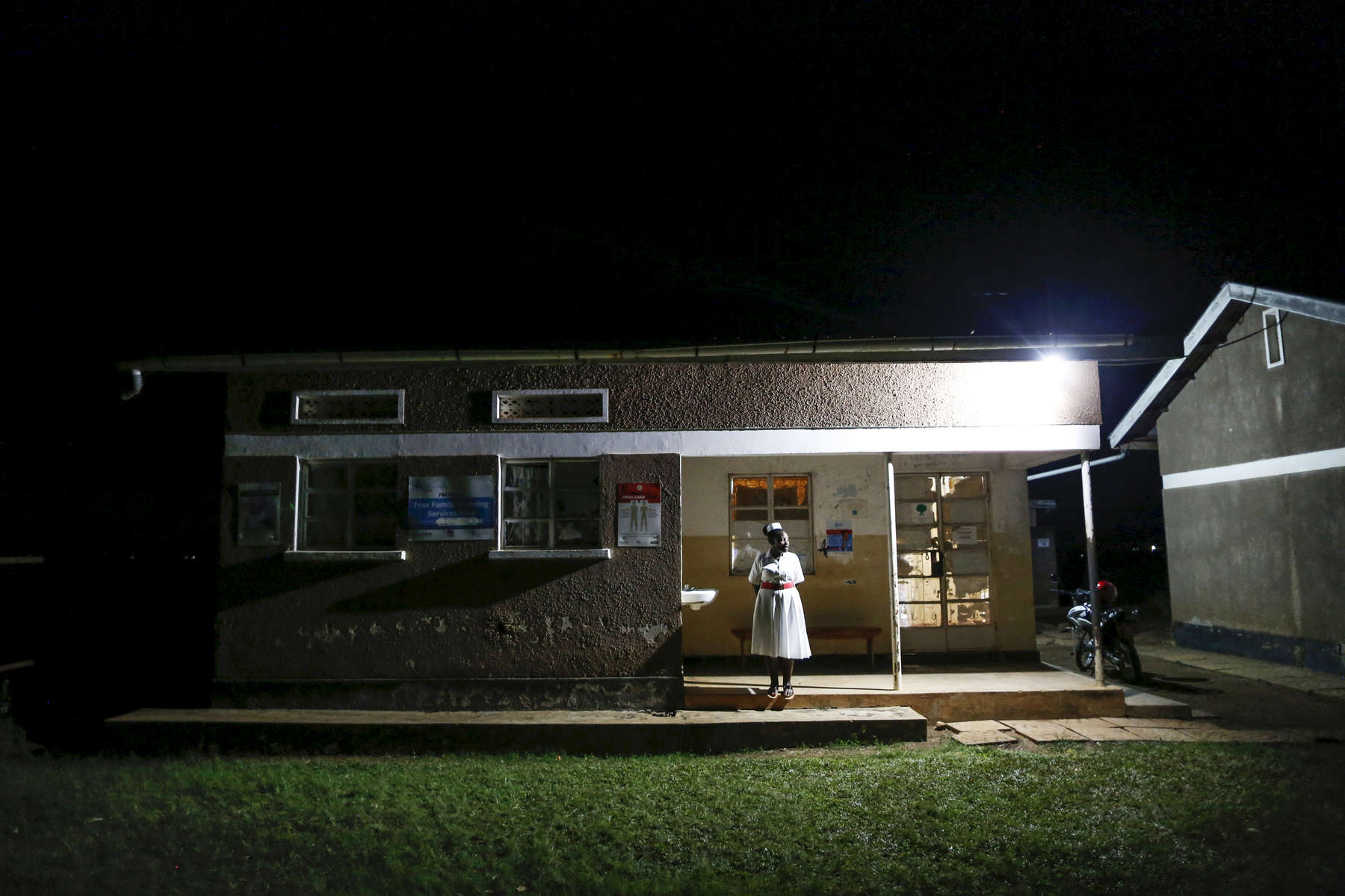 Jacqueline Cosslin, a midwife, stands outside of a maternity clinic lit by a solar panel in the district of Rakai, Uganda on December 6, 2018. In Africa, the development of solar panels technology has greatly improved the quality of life of people who previously had to use more expensive dangerous and less efficient options, like candles, petrol lamps, flashlights, or nothing at all.