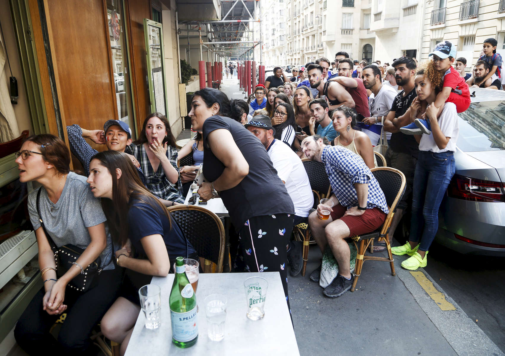 Supporters try to watch the World Cup Soccer final on the TV screen of a bar, on July 15, 2018, in Paris, France.On the historical Soccer World Cup final between France and Croatia, fans were invited to watch the game on giant screens set up in the Champs de Mars, in front of the Eiffel Tower in Paris. But this Fan Zone was full long before the start of the game, leaving thousand of supporters scrambling to find a place to watch the game close by. The nearby and usually quiet coffees and restaurants were quickly over flooded. But for the next two and a half hours, it did not matter to watch the game from the middle of the streets. Very few cars were circulating, because almost everyone in France was watching, or trying to watch the game.