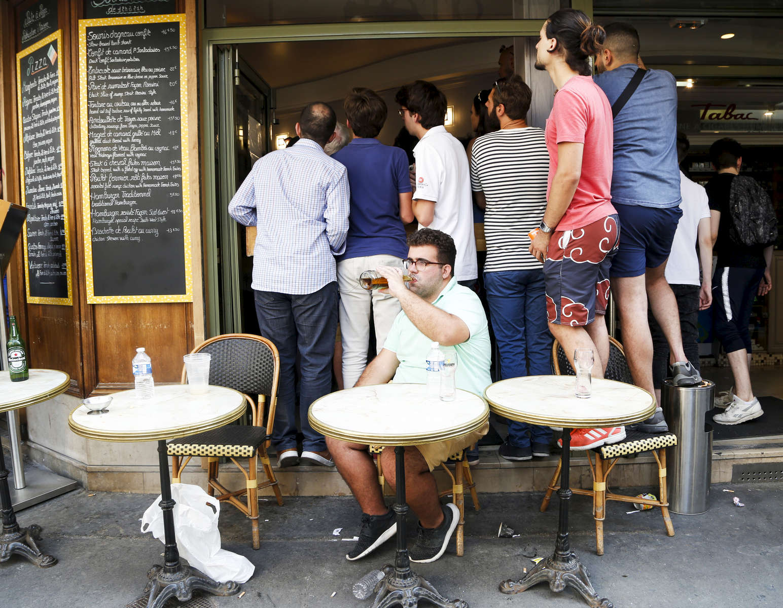 Supporters try to watch the World Cup Soccer final on the TV screen of a bar, on July 15, 2018, in Paris, France.