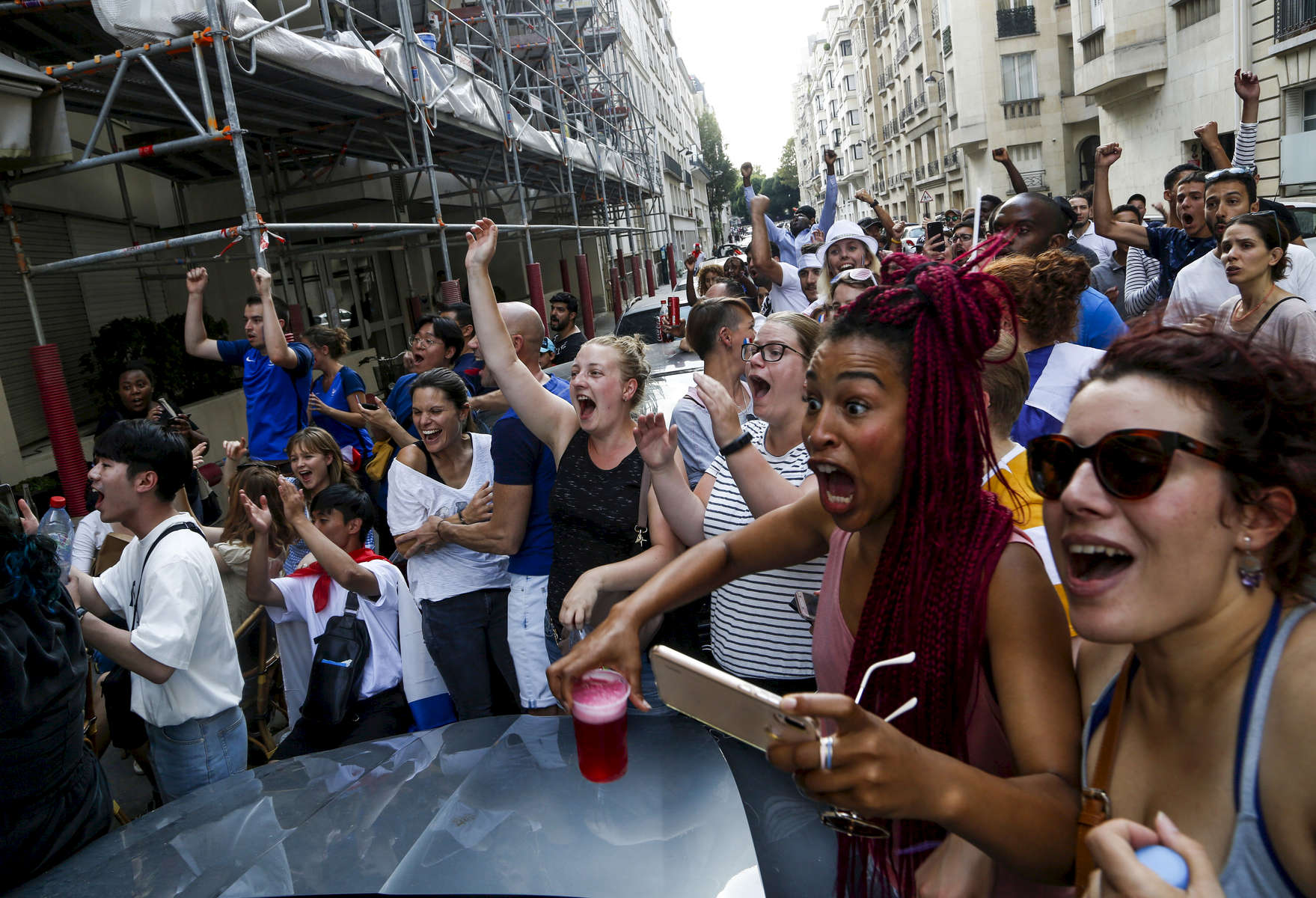 Supporters react when France strikes its first goal during the World Cup Soccer final on July 15, 2018, in Paris, France.On the historical Soccer World Cup final between France and Croatia, fans were invited to watch the game on giant screens set up in the Champs de Mars, in front of the Eiffel Tower in Paris. But this Fan Zone was full long before the start of the game, leaving thousand of supporters scrambling to find a place to watch the game close by. The nearby and usually quiet coffees and restaurants were quickly over flooded. But for the next two and a half hours, it did not matter to watch the game from the middle of the streets. Very few cars were circulating, because almost everyone in France was watching, or trying to watch the game.