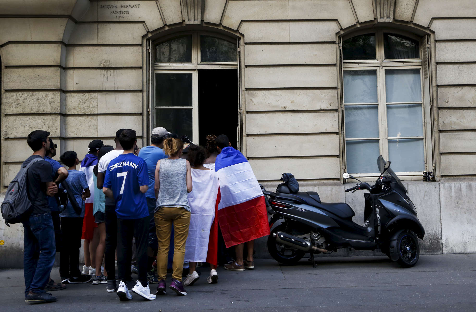 Supporters try to watch the World Cup Soccer final on the TV of a private apartment, on July 15, 2018, in Paris, France.On the historical Soccer World Cup final between France and Croatia, fans were invited to watch the game on giant screens set up in the Champs de Mars, in front of the Eiffel Tower in Paris. But this Fan Zone was full long before the start of the game, leaving thousand of supporters scrambling to find a place to watch the game close by. The nearby and usually quiet coffees and restaurants were quickly over flooded. But for the next two and a half hours, it did not matter to watch the game from the middle of the streets. Very few cars were circulating, because almost everyone in France was watching, or trying to watch the game.