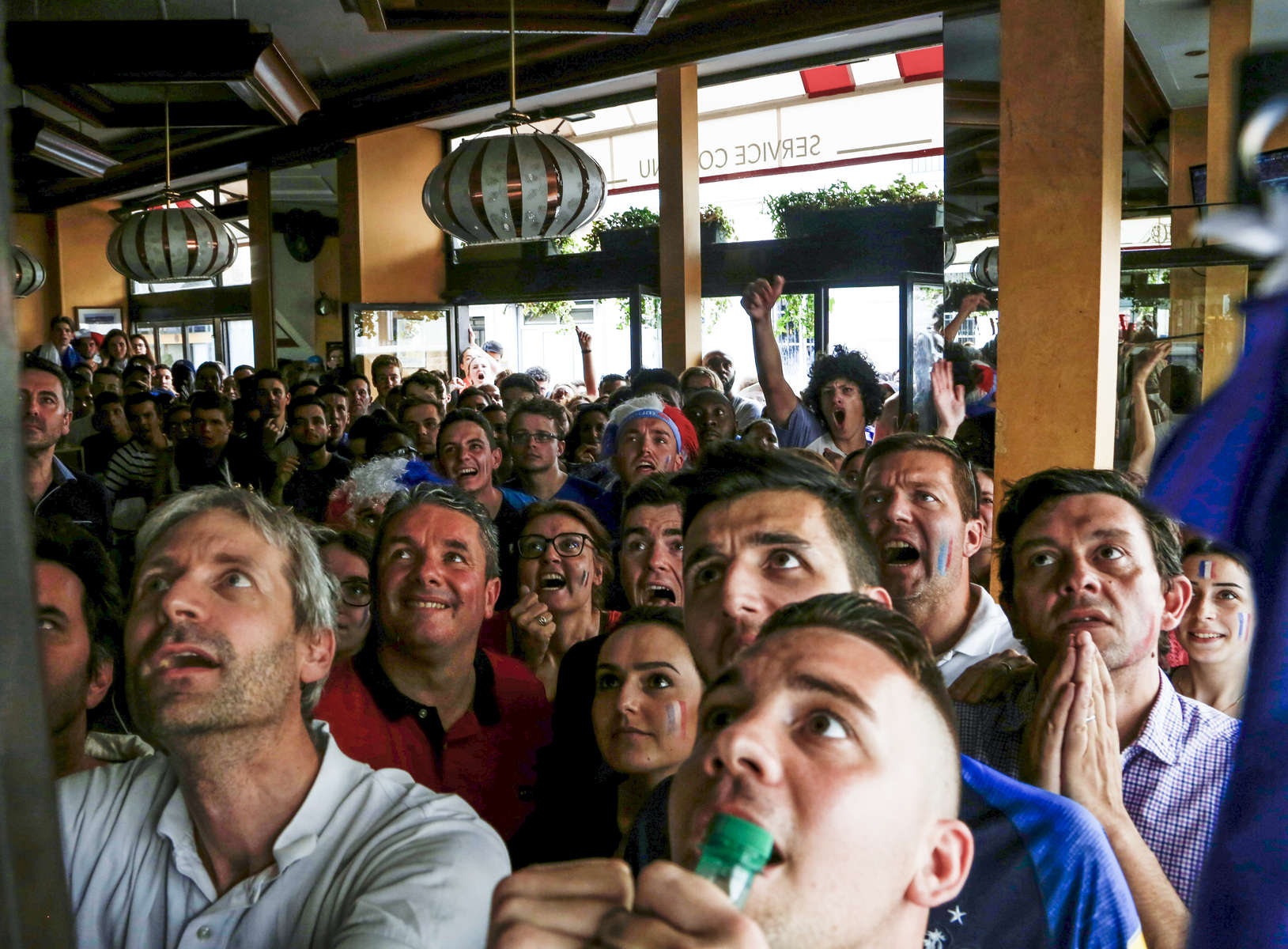 Supporters watch the World Cup Soccer final on the TV of a bar, on July 15, 2018, in Paris France.On the historical Soccer World Cup final between France and Croatia, fans were invited to watch the game on giant screens set up in the Champs de Mars, in front of the Eiffel Tower in Paris. But this Fan Zone was full long before the start of the game, leaving thousand of supporters scrambling to find a place to watch the game close by. The nearby and usually quiet coffees and restaurants were quickly over flooded. But for the next two and a half hours, it did not matter to watch the game from the middle of the streets. Very few cars were circulating, because almost everyone in France was watching, or trying to watch the game.