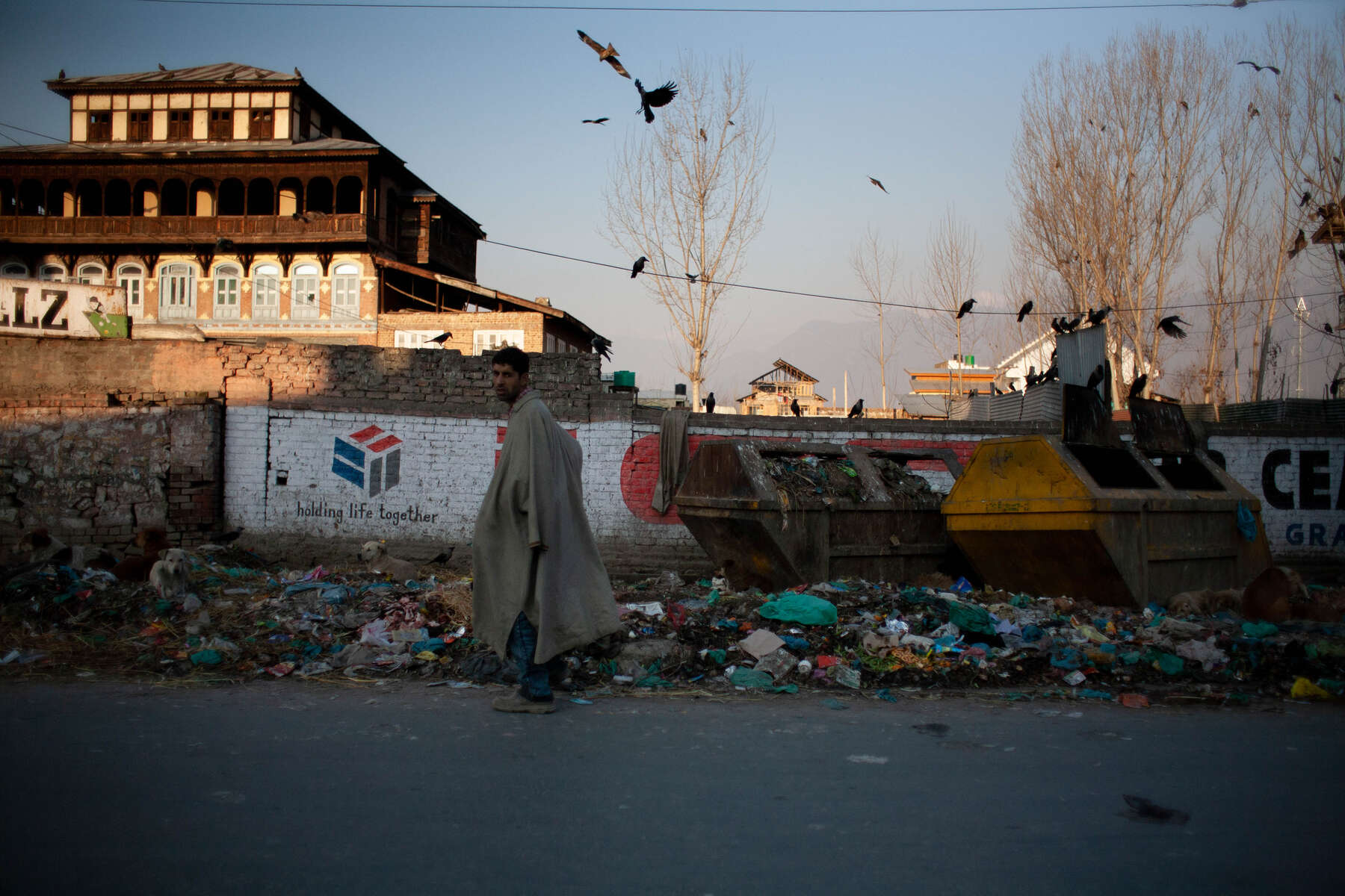 Snow melts over earth and waste. Bins stand beside piles of materials, expired, and without purpose; the decaying of Srinagar's 'shehr-e-Khaas'.