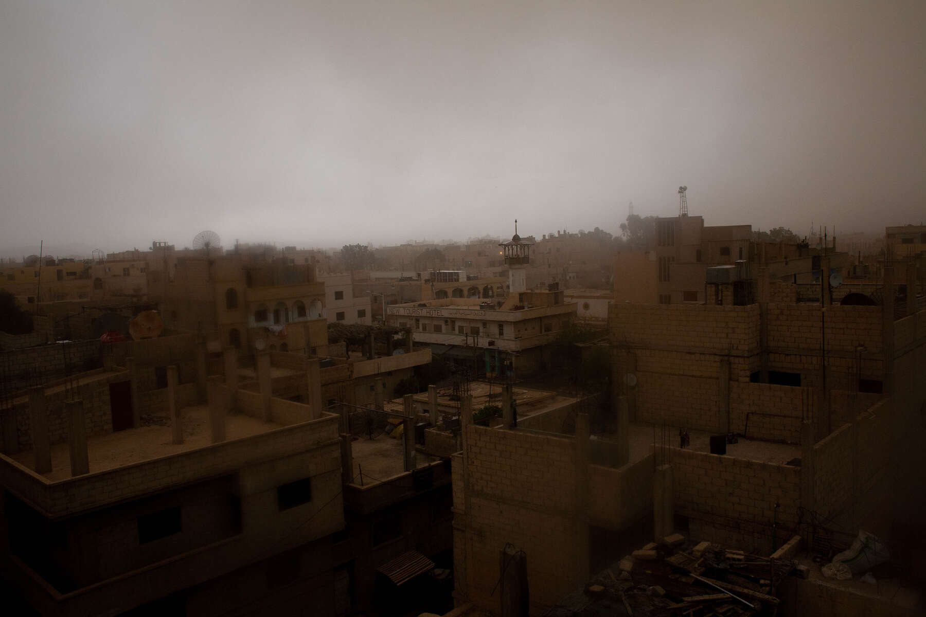 Sand storms rise with the setting of the desert sun. Rooftops bear the weight from the atmosphere as the evening settles under the Syrian sky.