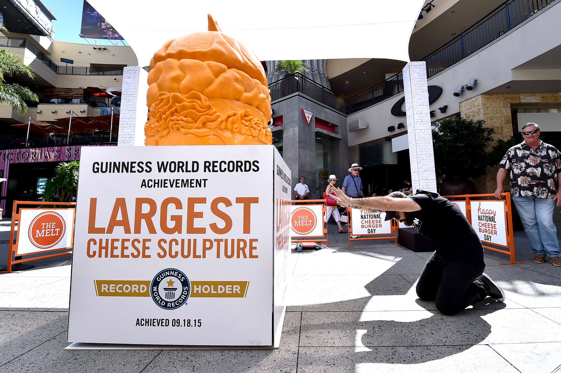 IMAGE DISTRIBUTED FOR THE MELT - Kyler Clark of Georgia pays homage to THE MELT's GUINNESS WORLD RECORDS® Largest cheese sculpture on Sept. 18, 2015, in celebration of National Cheeseburger Day. The Melt partnered with renowned cheese sculptor Troy Landwehr to create the 1,524 pound, record-breaking sculpture, fittingly carved in the shape of a cheeseburger, complete with a pickle on top. (Photo by Jordan Strauss/Invision for The Melt/AP Images)