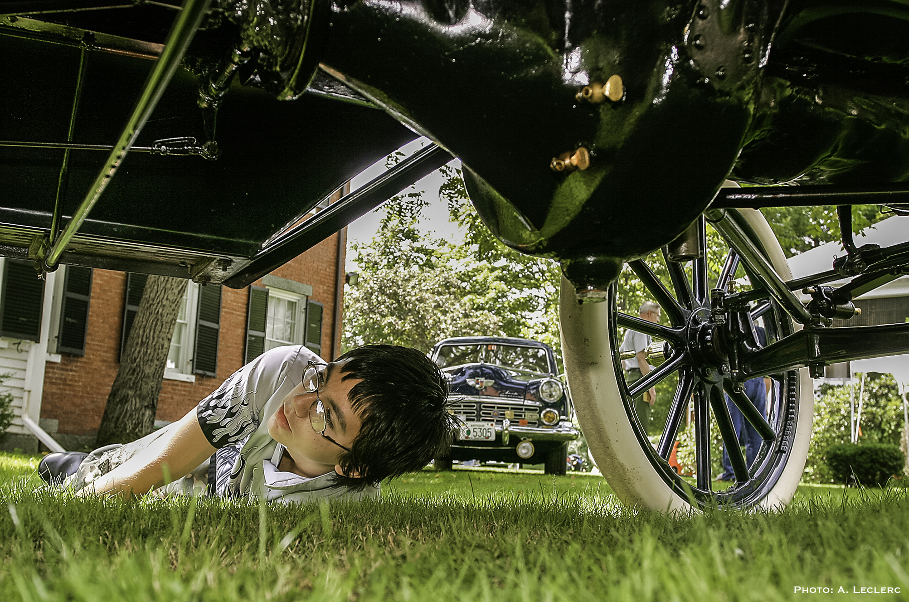 Aaron Leclerc/Staff photographerBrandon Rydell of Dover takes a look at the underside of a 1910 Ford Model T during Sundays' Antique/Classic Car show at the Woodman Institue Museum in Dover.
