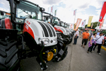 People walk past tractors at the 53rd agricultural fair Agra in Gornja Radgona, Slovenia, Aug. 22, 2015.