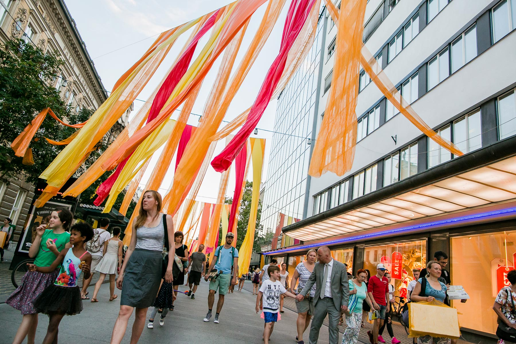 People walk through curtians of festival decoration during the 20th annual Ana Desetnica International Street Theatre Festival in Ljubljana, Slovenia, July 6, 2017.