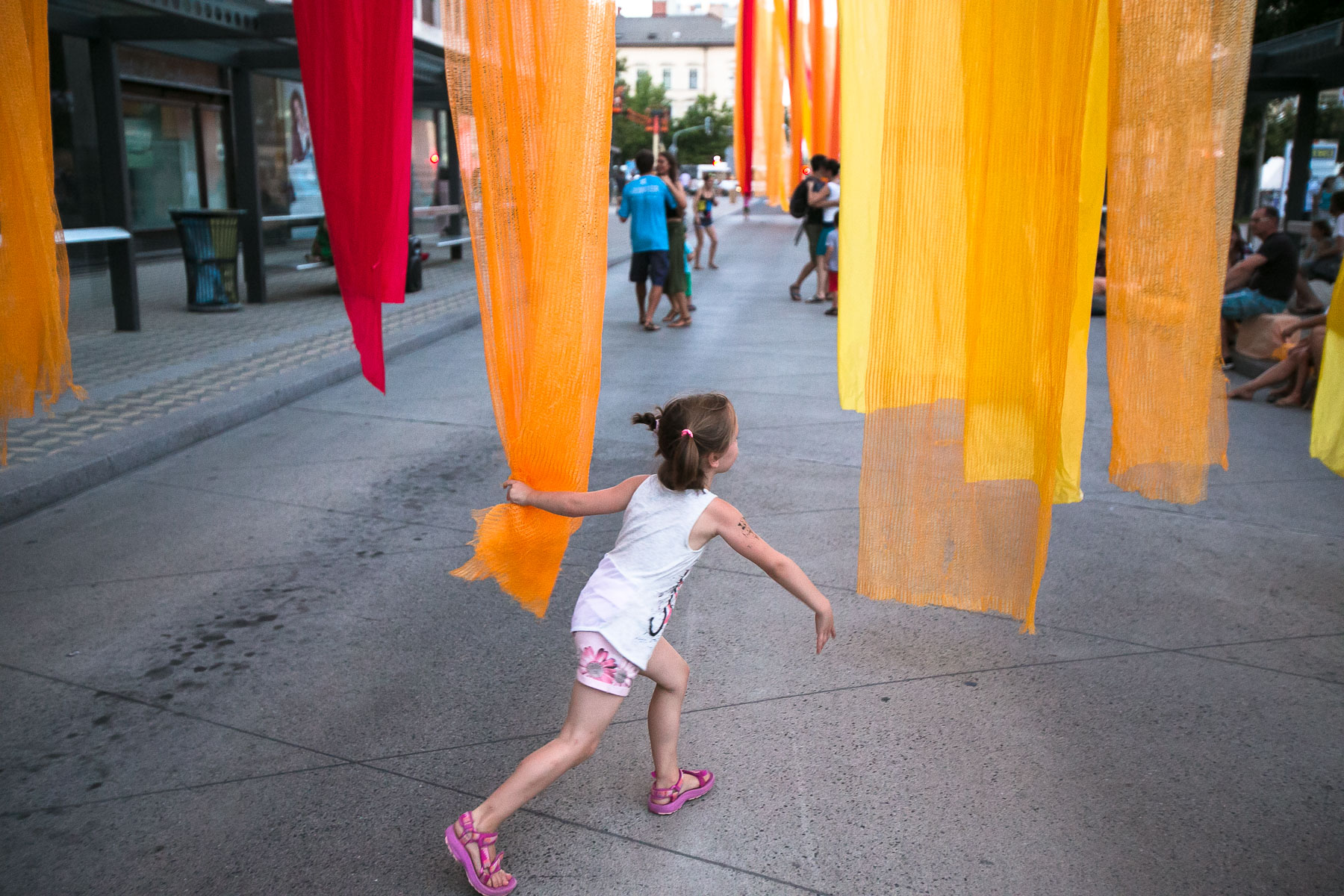 A girl plays with curtains of festival decoration during the 20th annual Ana Desetnica International Street Theatre Festival in Ljubljana, Slovenia, July 6, 2017.