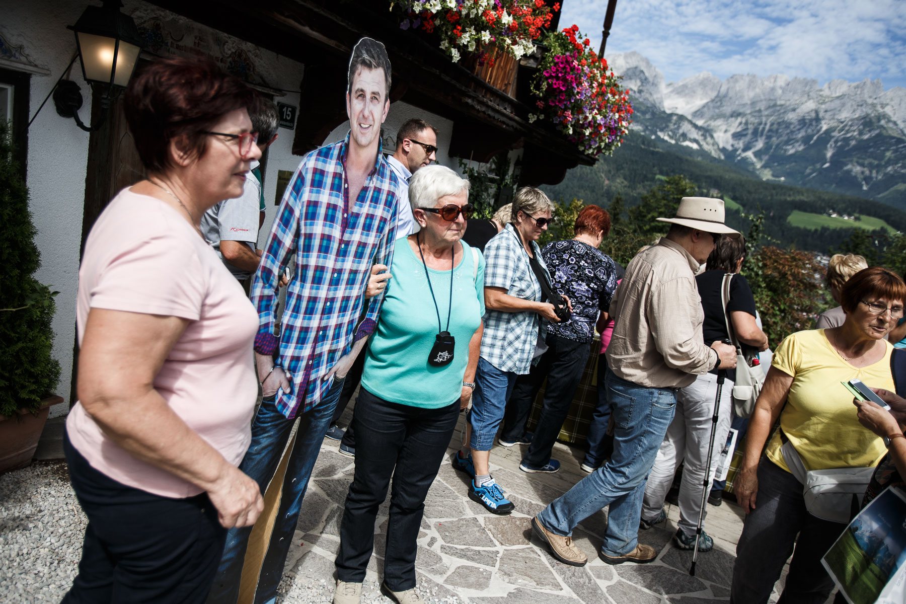 Slovenski turisti med fotografiranjem s podobo dr. Martina Gruberja iz serije Gorski zdravnik pred hišo v Ellmauu, ki služi kot njegova ordinacija v seriji. // Slovenian tourist take pictures with a cardboard cutout of dr. Martin Gruber from the series Der Bergdoktor (Mountain Medic) in front of the house that serves as his office in Ellmau, Tyrol.