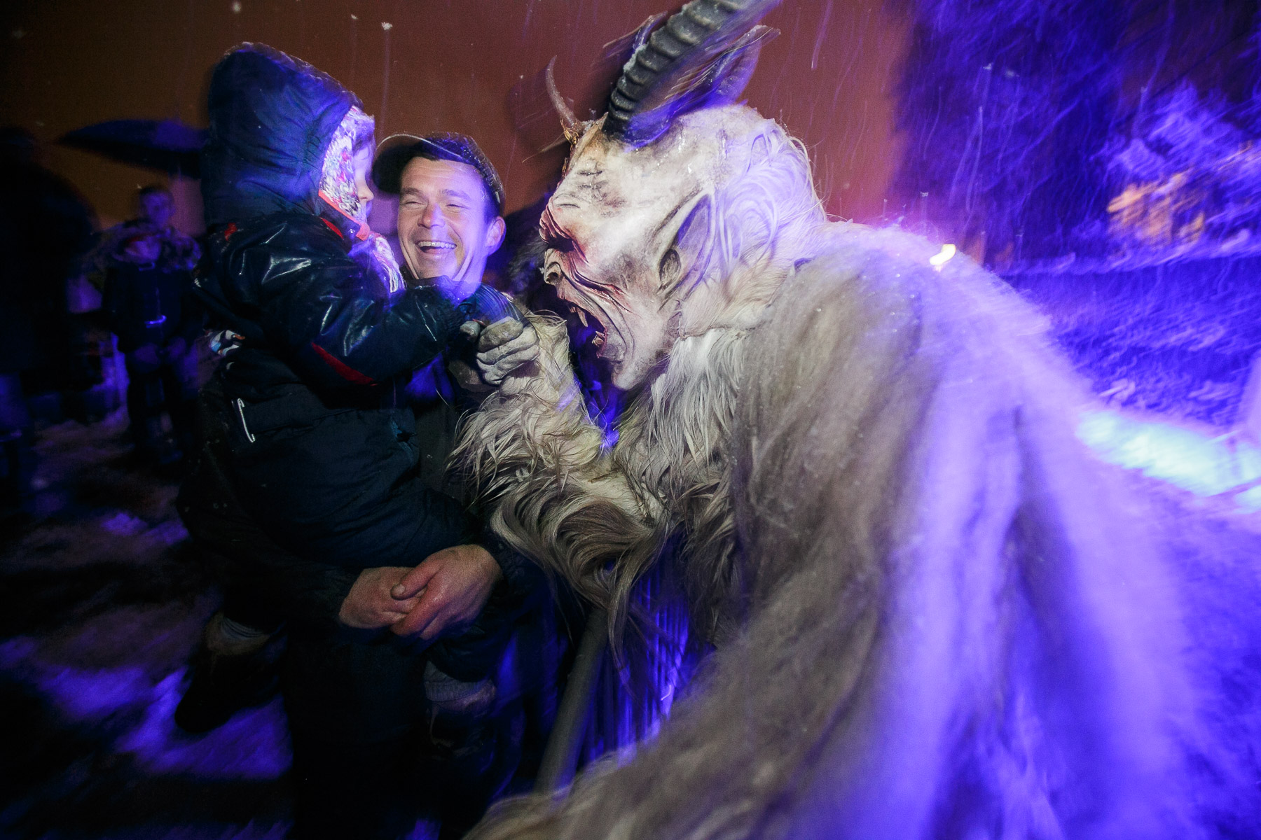 A participant dressed as the Krampus creature greets a child during the Krampus gathering in Goricane, Slovenia, Nov. 21, 2015. In Central European alpine folklore, Krampus is a demonic creature traditionally following St. Nicholas and angels on the evening of December 5. It pries on children who were not good during the year.