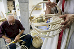Women observe an unfinished basket as a man prepares wicker at the 40th traditional woodenware fair in Ribnica, Slovenia, Sep. 6, 2015.