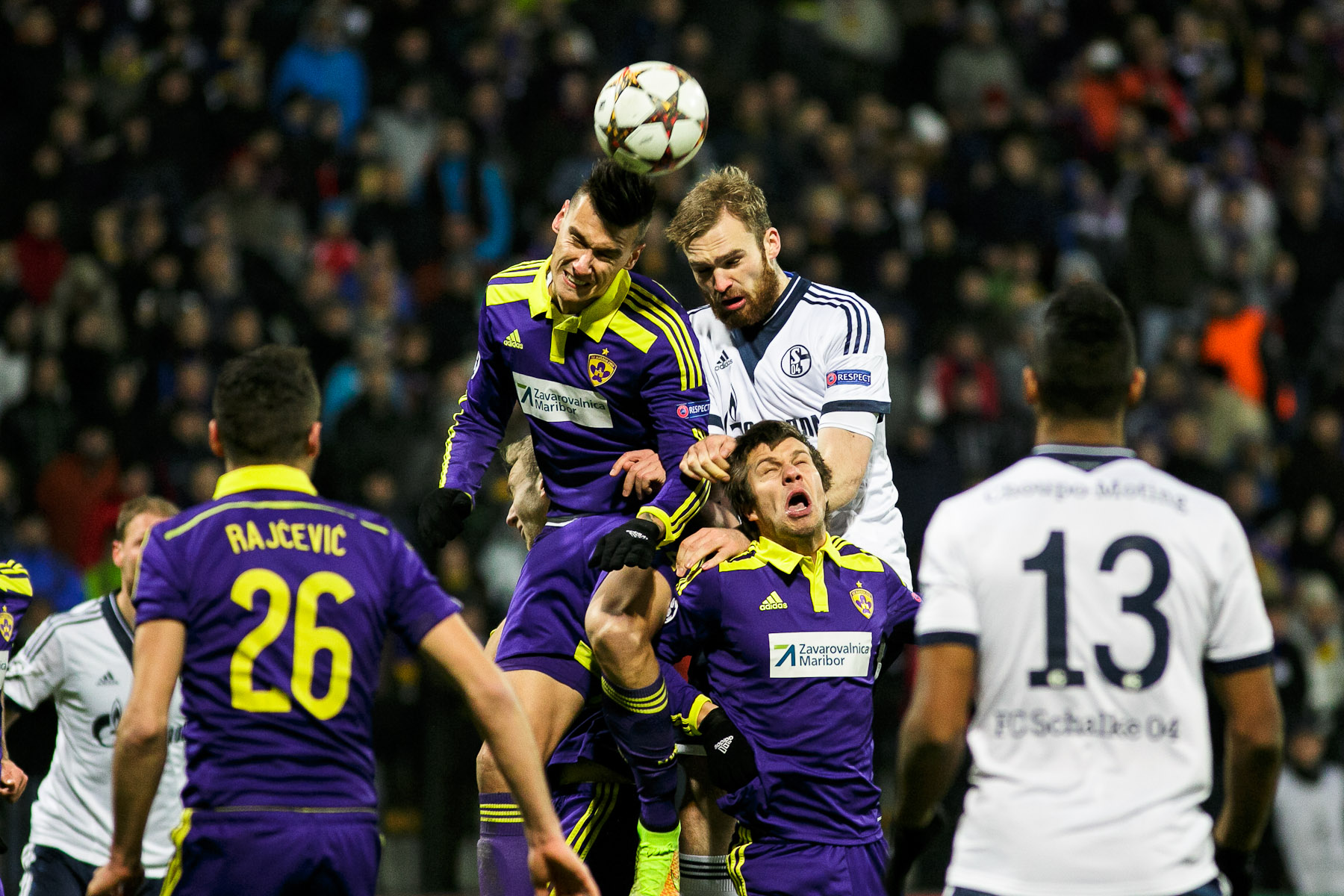 Jan Kirchhoff of FC Schalke 04 and Arghus of NK Maribor jump for the ball during the UEFA Champions League Group G match on December 10 in Maribor, Slovenia.